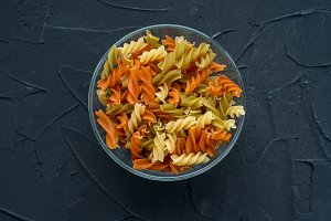 Multicolor spiral macaroni pasta in a glass bowl on a black textured background, in the center close-up from the top.