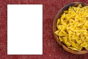 farfalle macaroni pasta in a wooden bowl on a red brown rustic texture background with a side. Close-up with the top. White space for text and ideas.