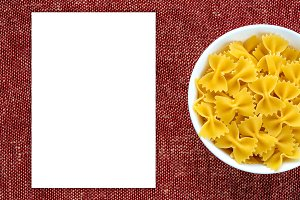 farfalle macaroni pasta in a white cup on a red brown rustic texture background, in the center close-up from the top. White space for text and ideas.