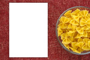 farfalle pasta in a glass bowl on a red brown rustic texture background, in the center close-up from the top macaroni. White space for text and ideas.