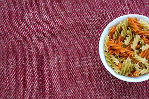 Multicolor spiral macaroni pasta in a white bowl on a red brown rustic texture background with a side. Close-up with the top. With space for text.
