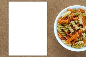 Multicolor spiral macaroni pasta in a white bowl on a brown rustic background texture with a side. Close-up with the top. White space for text and ideas.
