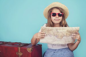 little girl with suitcase and map