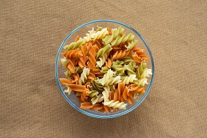 Multicolor spiral macaroni pasta in a glass bowl on a brown rustic texture background, in the center from the top.