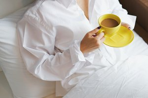 Woman and coffee morning on bed