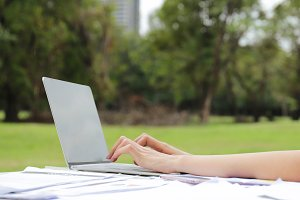 Woman typing on laptop in garden