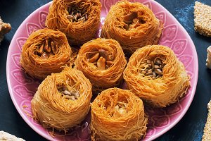 Arabic sweets. A variety of oriental sweets on a blue background. Baklava, halva, sherbet, sesame.