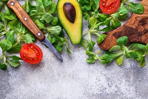 Green food background with corn lettuce, tomato and avocado