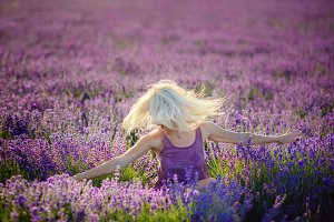 Beautiful girl in a field of lavender on sunset.