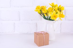 Jar with narcissuses and a gift box