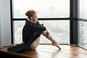 Ballerina is sitting by window
