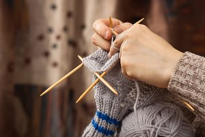 hands of woman knitting a sock