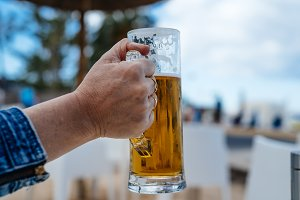 Hand of woman holding a pint of cold beer against blurred beach