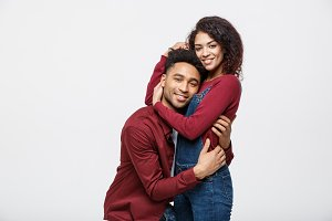 portrait of happy african american couple hug each other on white background.