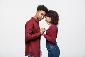 Side view of beautiful African American young couple in classic shirts holding hands, looking at each other and smiling.