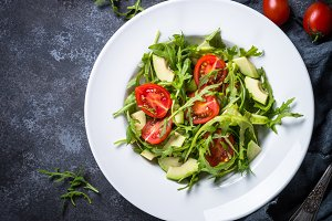 Green salad from arugula, avocado and tomatoes.