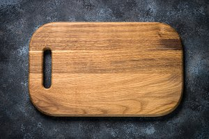 Wooden cutting board on black stone table top view.