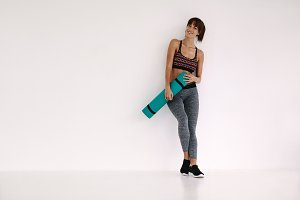 Smiling woman with yoga mat