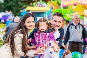Father, mother, daughter enjoying fun fair ride, amusement park