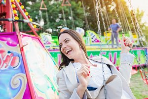 Young woman on chain swing ride, amusement park