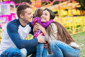 Daughter hugging her mother, happy family in amusement park