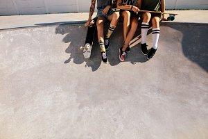 Legs of female skaters sitting