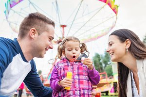 Father, mother, daughter blowing bubbles, amusement park, fun fa