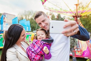 Father, mother and daughter in amusement park taking selfie