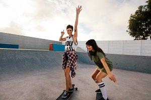 Female friends skateboarding