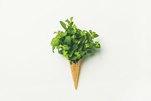 Waffle cone with fresh mint leaves over white background, flat-lay