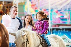 Girl enjoying pony ride, fun fair, parents watching her