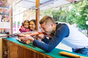 Father playing shooting games at amusement park, family watching