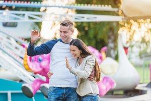 Parents at fun fair, waving their child taking ride