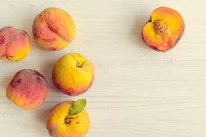 Ripe peaches on white wooden background