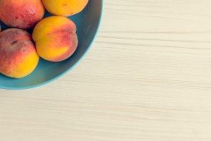 Ripe peaches in blue bowl