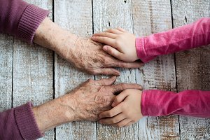 Hands of unrecognizable grandmother and her granddaughter