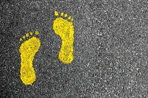 Yellow footprints on asphalt
