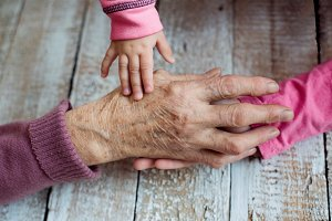 Hands of unrecognizable grandmother and her granddaughters