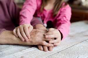 Hands of unrecognizable granddaughter and her grandmother