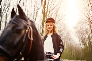 blonde girl riding on horse
