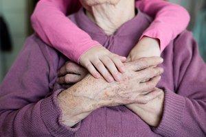 Unrecognizable granddaughter holding hands of her grandmother