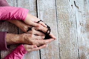 Hands of unrecognizable grandmother and her granddaughter holding rosary