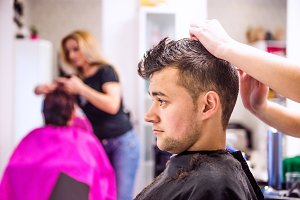 Professional hairdresser making new haircut to her handsome clie