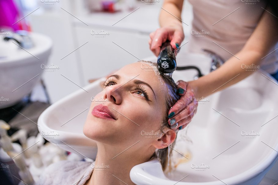 Unrecognizable Professional Hairdresser Washing Hair To Her Clie People