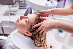 Unrecognizable professional hairdresser washing hair to her clie