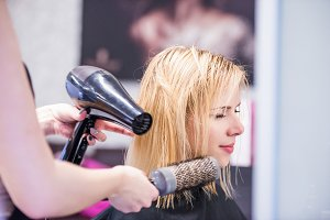 Unrecognizable hairdresser drying hair of her beautiful young cl