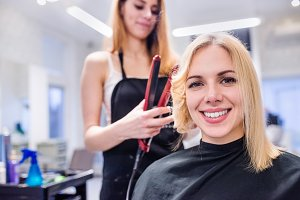 Unrecognizable hairdresser creating hairstyle for her beautiful