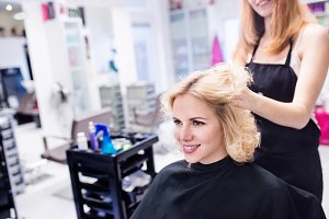 Hairdresser making a new haircut to her handsome client