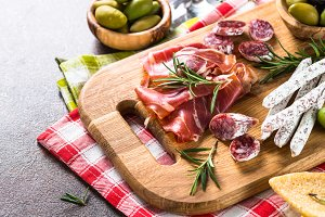 Antipasto delicatessen - sliced meat, ham, salami and olives on