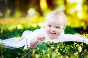 a beautiful baby with blue eyes lies on the green grass in the Park at sunset in the sunlight. Smiling, looking straight into the camera.